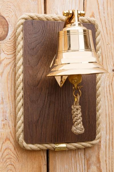 Schiffsglocke auf Holztafel